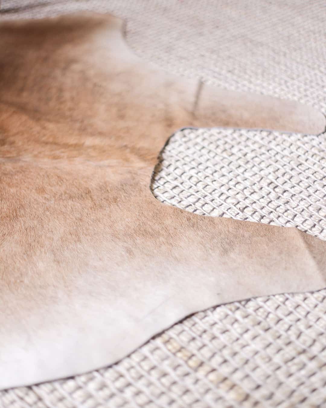 how-to-layer-cowhide-over-area-rug